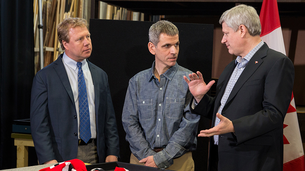 Prime Minister Stephen Harper, joined by Rick Dykstra, Member of Parliament for St. Catharines, frames a hockey jersey at Framecraft Ltd. with help from Joe Mancino, owner of Framecraft Ltd., prior to announcing improved access to financing for Canadian small businesses.