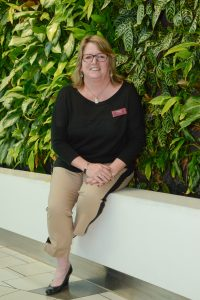 Peggy Howard, General Manager of GTC in front of the Living Wall.   Photo by Ray Hudson