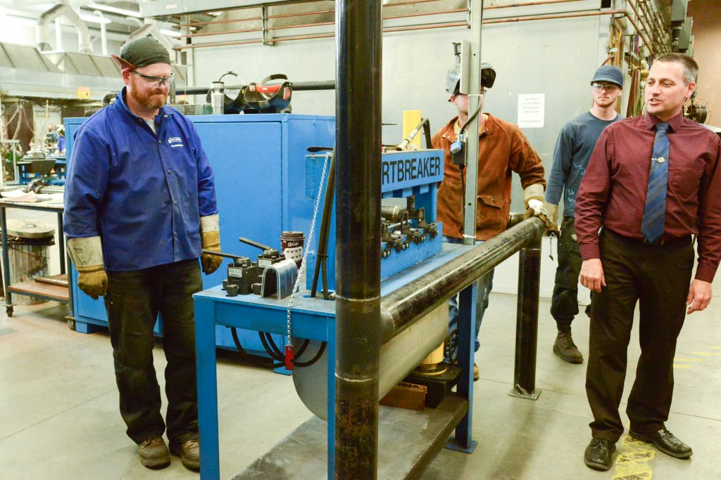 Dean Brian Haugen explains a weld failure pressure test to Surrey Board of Trade visitors to the welding lab.    Photo by Ray Hudson