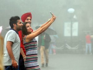 File photo of Indian teenagers taking a rain-drenched selfie in New Delhi. ( Photo.. IANS)