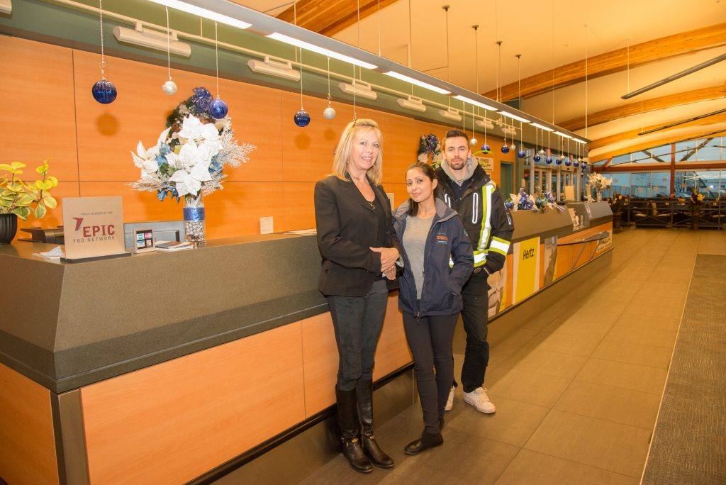From left, Heather Braun, Airport General Manager, Safety Officer Navdeep Kaur and Brandon Walker-Shaw, Operations Supervisor stand by the ticket counter, decorated for the season. Photo: Ray Hudson