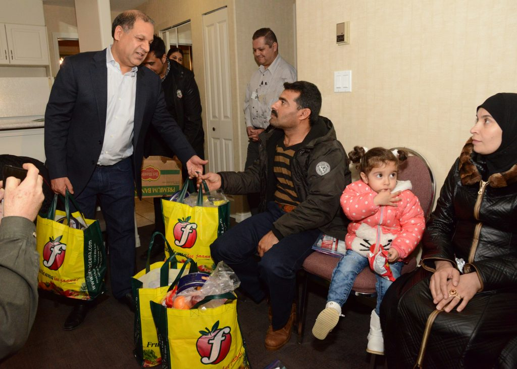 Tony Singh gives the first bags of groceries to Syrian family. Photos by Ray Hudson