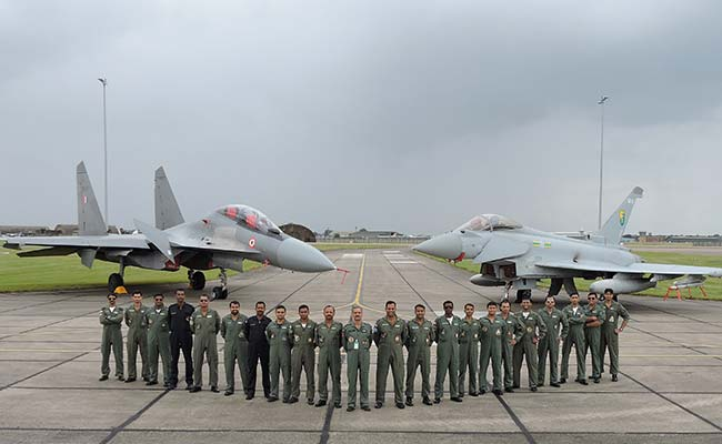 The IAF team which participated in the air combat exercise, with both the fighter planes in the background. The Sukhoi Su-30 is on the left. (Image courtesy NDTV)