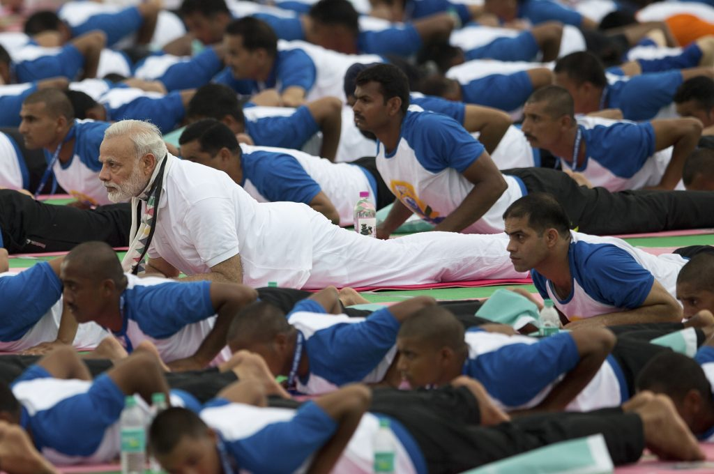 Indian Prime Minister Narendra Modi, center, performs yoga along with thousands of Indians in Chandigarh, India, Tuesday, June 21, 2016. Millions of yoga enthusiasts are bending their bodies in complex postures across India as they take part in a mass yoga program to mark the second International Yoga Day. (AP Photo/Saurabh Das)