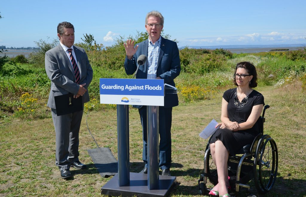 Panorama MLA, Marvin Hunt at the podium presents the dike improvement project details, along with the Hon. Stephanie Cadieux, Cloverdale and Minister of Children and Family Development, and City Councillor Mike Starchuk.