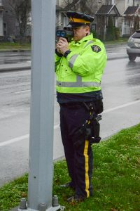 Despite the speed zone signs and digital speed displays, Const. Sid Jordan steps out to direct a speeder into a safe area to receive a speeding ticket.