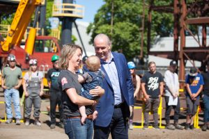 1.Premier John Horgan and Danielle Shaw, a young mother and ironworker apprentice with Local 97, celebrates the Community Benefits Agreement announcement with workers at the British Columbia Institute of Technology. Photo credit: Government of British Columbia.