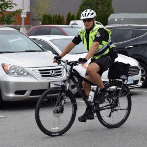 Constable Miller biking through a parking lot.